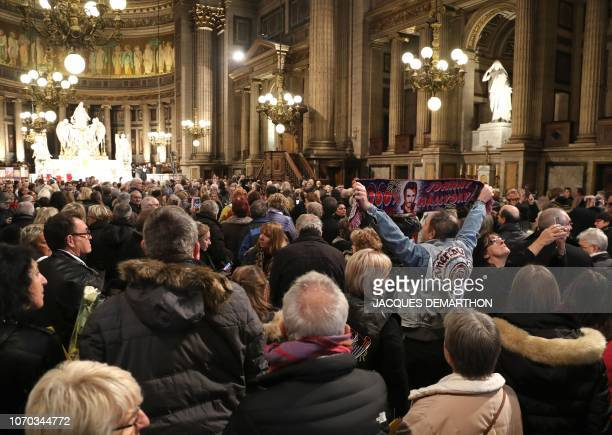 Fans attend a mass in tribute to French rock singer Johnny Hallyday in Paris on December 9 2018 one year after Johnny's death French music icon...