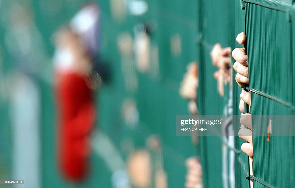 Fans behind a fence watch the French national football team players during a training session, on May 24, 2010, near Tignes in the French Alps, as part of the preparation for the upcoming World Cup 2010. France will play against Uruguay in Capetown in its group A opener match on June 11.