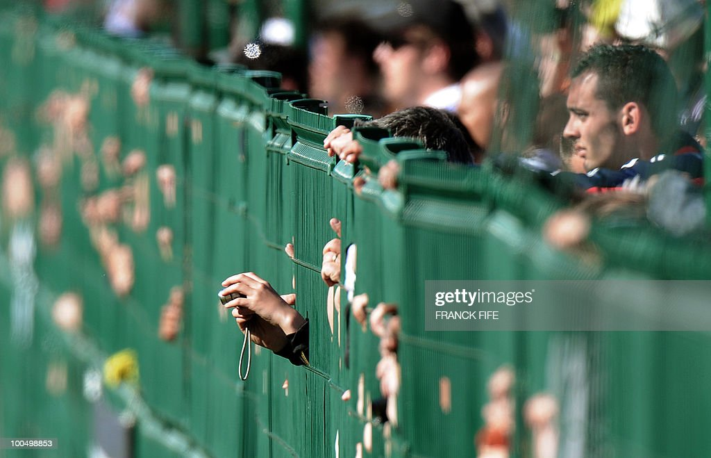 Fans behind a fence watch the French nat