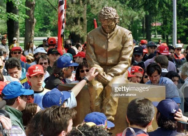 Fans berühren am an der Formel-1-Rennstrecke von Imola eine Bronzestatue des vor drei Jahren hier tödlich verunglückten brasilianischen Weltmeisters...