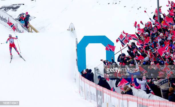 Fans brandish the Norwegian flag while Norway's Therese Johaug celebrates as she wins the ladies Holmenkollen Cross Country 30 km freestyle mass...