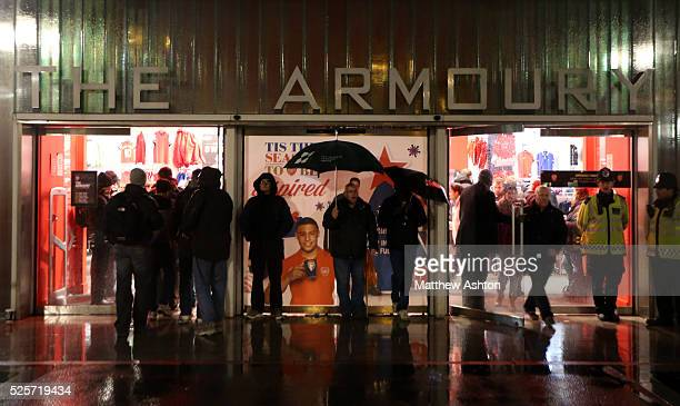 Fans brave the rain with their umbrellas at the Armoury shop at the Emirates stadium home of Arsenal