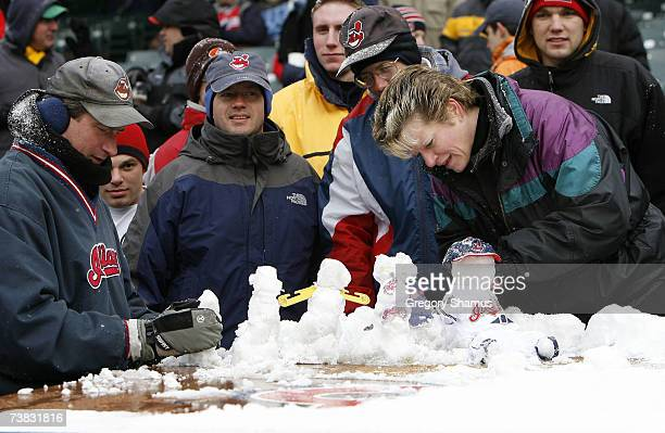 Fans build snowmen on top of the Seattle Mariners dugout during a weather delay at the Home Opener for the Cleveland Indians on April 6 2007 at...