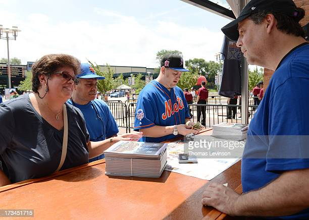 Fans buy programs prior to the 2013 SiriusXM All-Star Futures Game at Citi Field Sunday, July 14 in the Flushing neighborhood of the Queens borough...