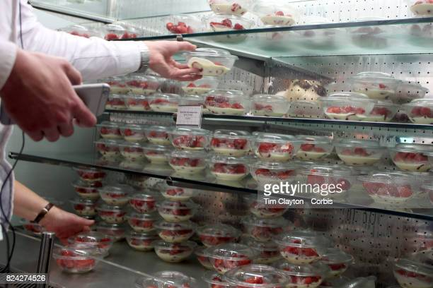 Fans buying strawberries on Men's Final Day during the Wimbledon Lawn Tennis Championships at the All England Lawn Tennis and Croquet Club at...