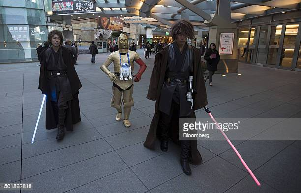 Fans carry lightsabers and wear costumes ahead of the first public screening of Walt Disney Co's Star Wars The Force Awakens at TOHO Cinemas Roppoing...