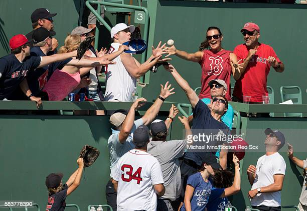 Fans catch a home run hit by Xander Bogaerts of the Boston Red Sox pitches against the Detroit Tigers in the seventh inning on July 27 2016 at Fenway...