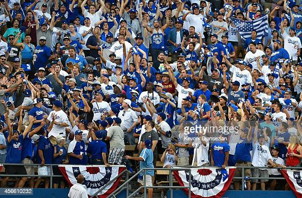 Fans catch the ball on a two run homerun by AJ Ellis of the Los Angeles Dodgers in the fifth inning during Game One of the National League Division...