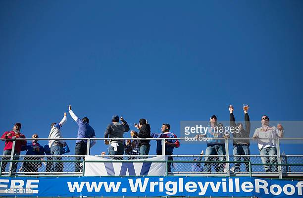 Fans celebrate a secondinning home run as they watch from the roof of a building across from Wrigley Field as the Chicago Cubs play the St Louis...