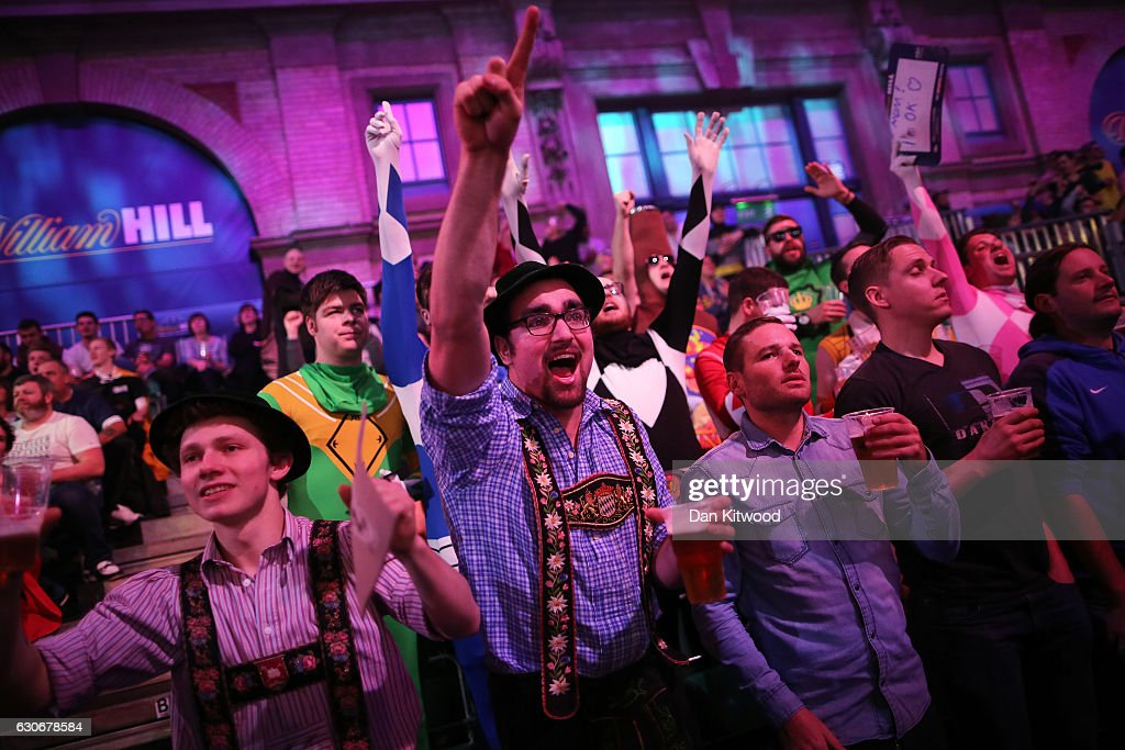 Fans celebrate after Peter Wright from Scotland threw a 180 during the quarter final of 2016 William Hill World Darts Championship on December 30, 2016 in London, England. The event is world's biggest darts tournament, with 72 players from across the globe competing across 15 days of the knock out competition.