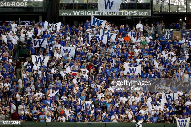 Fans celebrate after the Chicago Cubs beat the Washington Nationals 21 in game three of the National League Division Series at Wrigley Field on...