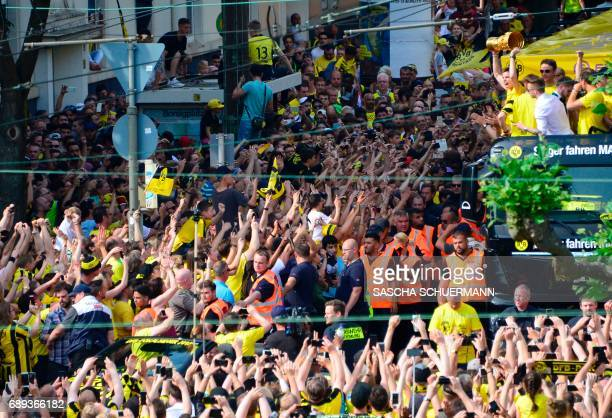 Fans celebrate as Dortmund's midfielder Julian Weigl lifts the trophy on a truck with the team of BVB Borussia Dortmund during celebrations after...
