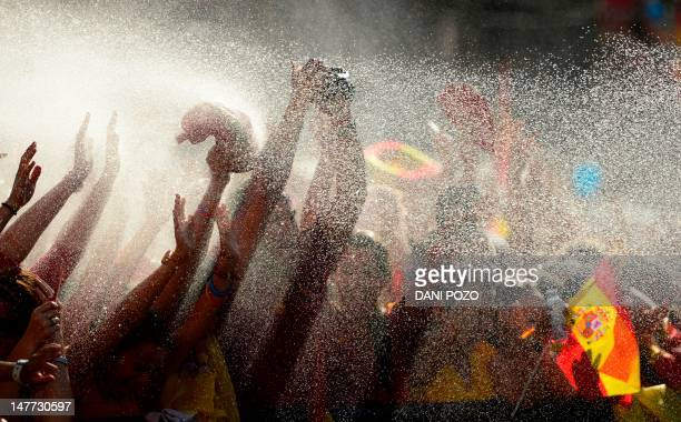 Fans celebrate as the Spanish national football team arrives on Cibeles Square on July 2 2012 after parading through Madrid a day after it won the...