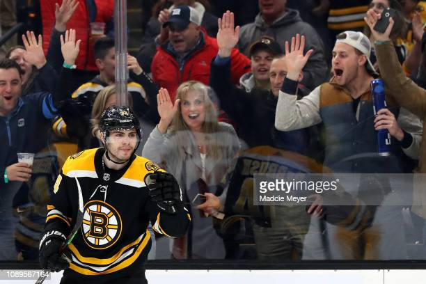 Fans celebrate behind Jake DeBrusk of the Boston Bruins after he scored a goal against the Calgary Flames during the third period at TD Garden on...