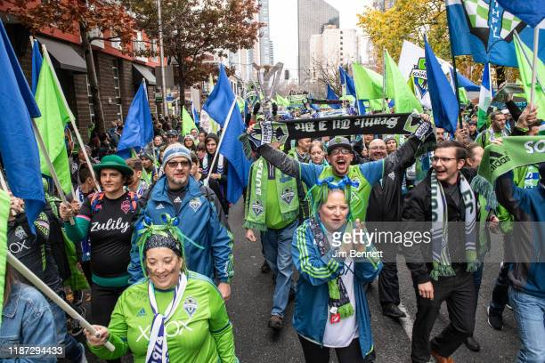 Fans celebrate in the street during the Seattle Sounders MLS Cup victory parade and rally on November 12 2019 in Seattle Washington