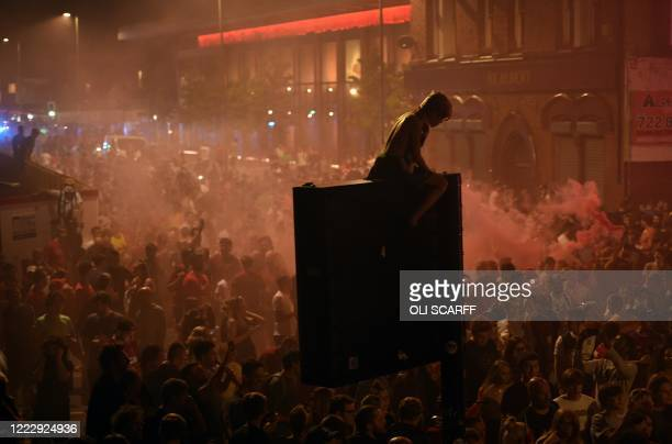 Fans celebrate Liverpool winning the Premier League title outside Anfield stadium in Liverpool, north west England on June 25 following Chelsea's 2-1...