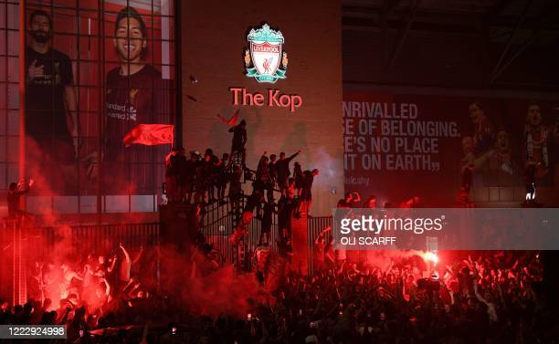 TOPSHOT Fans celebrate Liverpool winning the Premier League title outside Anfield stadium in Liverpool north west England on June 25 following...