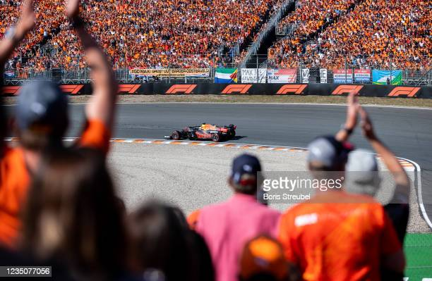 Fans celebrate Max Verstappen of the Netherlands driving the Red Bull Racing RB16B Honda during the F1 Grand Prix of The Netherlands at Circuit...