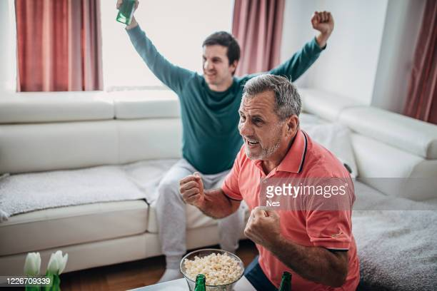 fans celebrate the victory in front of the tv - world sports championship stock pictures, royalty-free photos & images