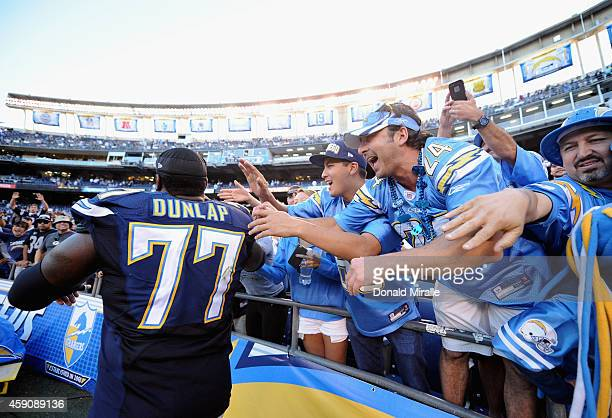 Fans celebrate with King Dunlap of the San Diego Chargers after their team defeated the Oakland Raiders 13-6 in the game at Qualcomm Stadium on...