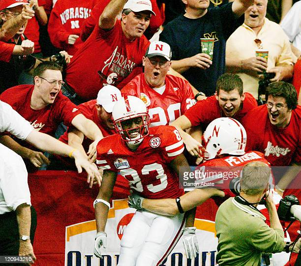Fans celebrate with Nebraska's Terrence Nunn and Todd Peterson after a touchdown by Nunn during the 2005 MasterCard Alamo Bowl game game between the...