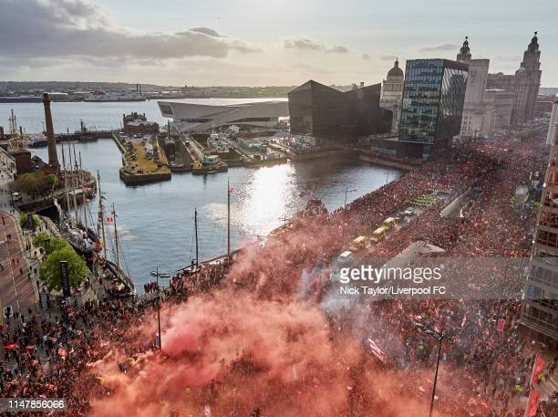 Fans celebrate with the Liverpool team during the open-top bus parade to celebrate winning the UEFA Champions League on June 2, 2019 in Liverpool,...