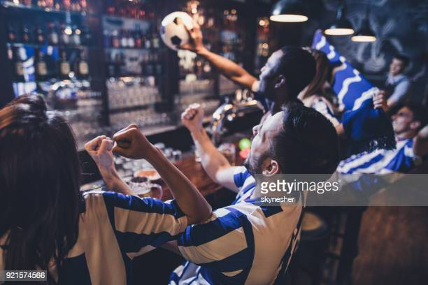 Supporters célébrant la victoire de leur équipe de football tout en regardant un match à la télévision dans un bar.