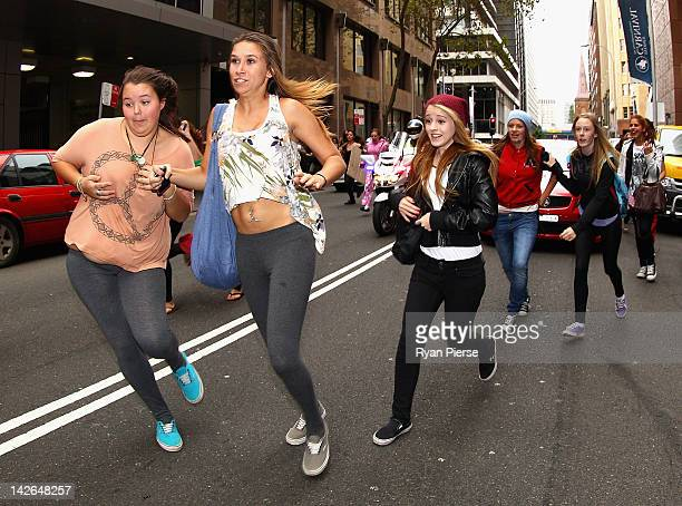 """Fans chase the One Direction car as they leave the """"Sunrise"""" studios at Martin Place on April 11, 2012 in Sydney, Australia. One Direction kicks off..."""
