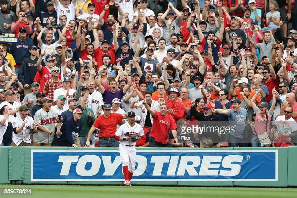 Fans cheer after Mookie Betts of the Boston Red Sox caught a ball hit by Josh Reddick of the Houston Astros in the second inning during game three of...
