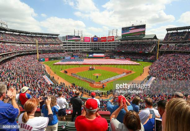 Fans cheer after the playing of the National Anthem before the Opening Day baseball game between the Houston Astros and the Texas Rangers at Globe...
