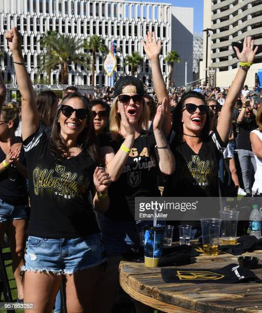 Fans cheer after watching singers perform the national anthems of the United States and Canada during a Vegas Golden Knights road game watch party at...