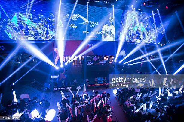 Fans cheer and wave batons as they watch the final round of the Electronic Arts Inc Sports FIFA Online Championship at the Nexon Co eSports Stadium...