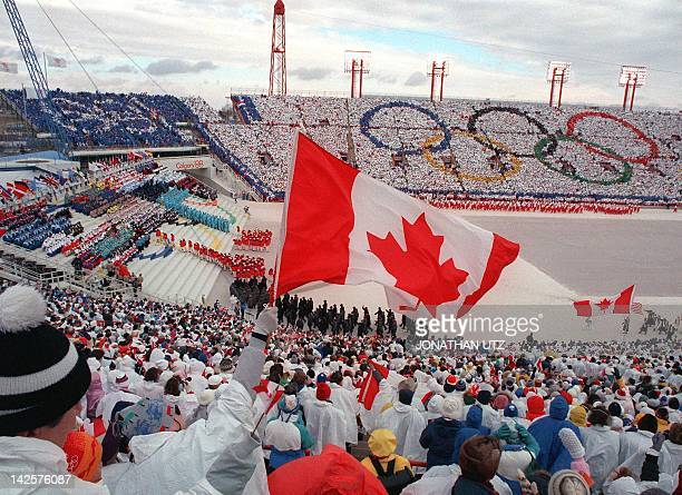 Fans cheer and wave flags as the Canadian delegation parades during the opening ceremony of the XVth Winter Olympic Games 13 February 1988 in Calgary...