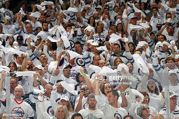 Fans cheer and wave white towels as part of the 'Whiteout' prior to puck drop between the Winnipeg Jets and the Anaheim Ducks in Game Four of the...