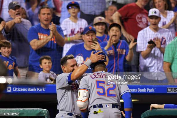 Fans cheer as Asdrubal Cabrera of the New York Mets pulls the helmet off of teammate Yoenis Cespedes after hitting his second home run of the game in...