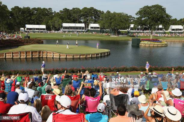 Fans cheer as Bill Haas of the United States makes birdie on the 17th green during the third round of THE PLAYERS Championship on the stadium course...