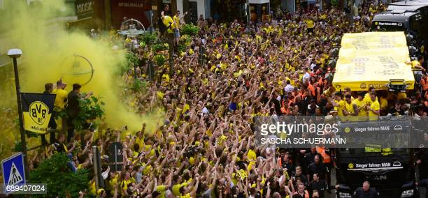 Fans cheer as Borussia Dortmund players arrive at Borsigplatz during celebrations after winning the German Cup final in Dortmund western Germany on...