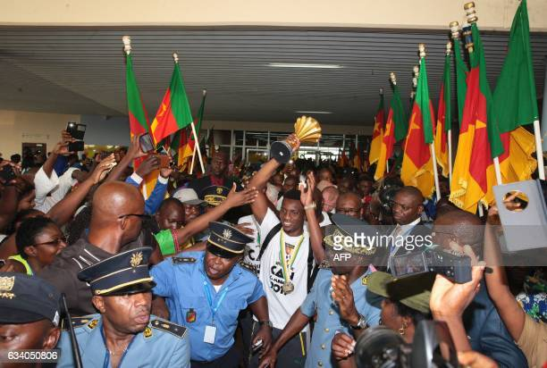 TOPSHOT Fans cheer as Cameroon's team captain and forward Benjamin Moukandjo holds up the winner's trophy as he and the national football team arrive...