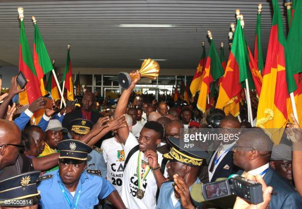 Fans cheer as Cameroon's team captain and forward Benjamin Moukandjo holds up the winner's trophy as he and the national football team arrive home to...