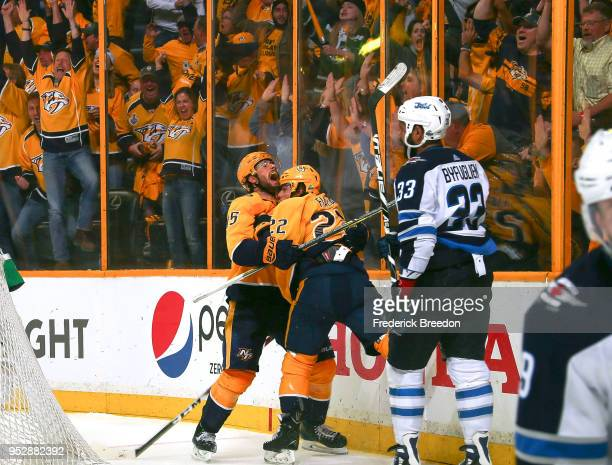 Fans cheer as Craig Smith congratulates teammate Kevin Fiala on scoring the game winning goal against Dustin Byfuglien the of the Winnipeg Jets in...