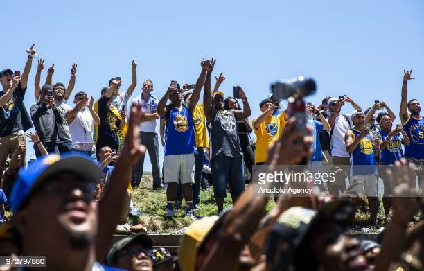 Fans cheer as Draymond Green of the Golden State Warriors passes by atop a double decker bus during the Golden State Warriors NBA Championship...