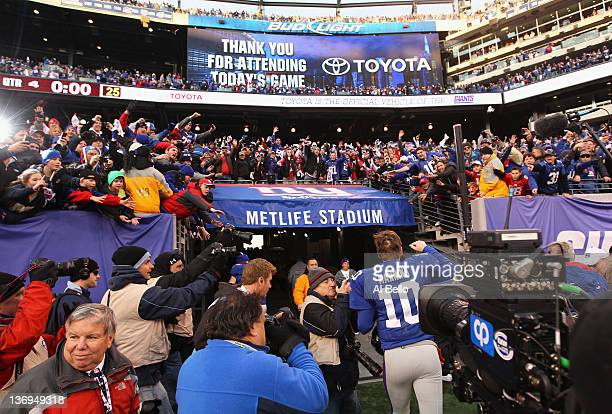 Fans cheer as Eli Manning of the New York Giants runs off of the field after the Giants won 24-2 against Atlanta Falcons during their NFC Wild Card...