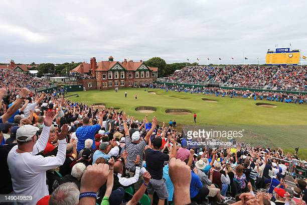 Fans cheer as Ernie Els of South Africa reacts to a birdie putt on the 18th green during the final round of the 141st Open Championship at Royal...