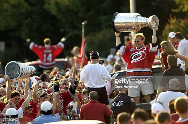 Fans cheer as Glen Wesley of the Carolina Hurricanes holds the Stanley Cup aloft during a parade to celebrate the team's game seven Stanley Cup...