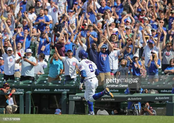 Fans cheer as Javier Baez of the Chicago Cubs runs the bases after hitting two run home run in the 7th inning against the San Diego Padres at Wrigley...