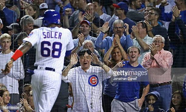 Fans cheer as Jorge Soler of the Chicago Cubs scores a run in the 6th inning on a single by Jason Heyward against the Pittsburgh Pirates at Wrigley...