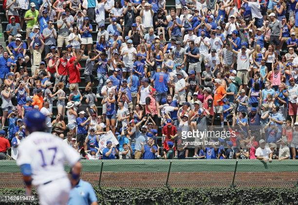 Fans cheer as Kris Bryant of the Chicago Cubs runs the bases after hitting a solo home run in the 1st inning against the Cincinnati Reds at Wrigley...