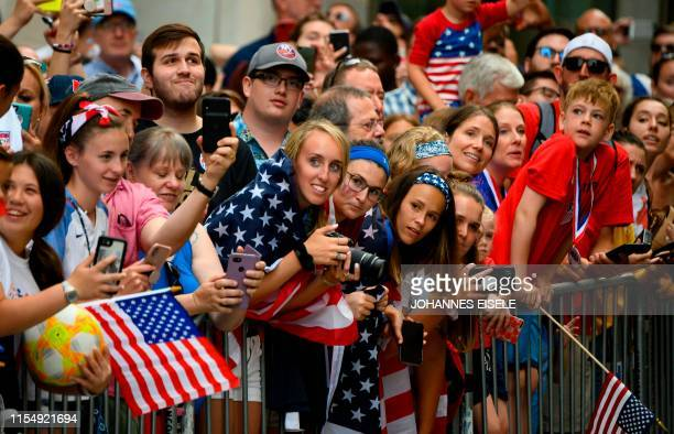 Fans cheer as members of the World Cupwinning US women's soccer team take part in a ticker tape parade for the women's World Cup champions on July 10...