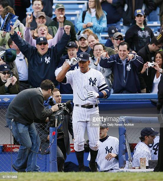 Fans cheer as New York Yankees' Alex Rodriguez comes out of the dugout for an interview after he hit a threerun walkoff homer to center in the bottom...