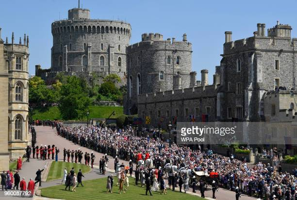 Fans cheer as Prince Harry, Duke of Sussex and the Duchess of Sussex ride a horse-drawn carriage after their wedding ceremony at St George's Chapel...